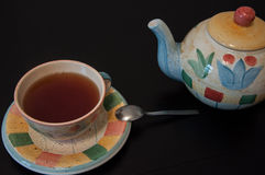 Cup of tea with teapot. Cup filled with tea and teapot with spoon Royalty Free Stock Photo