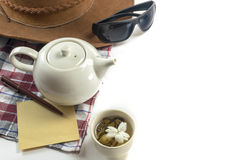 Cup of tea with teapot, hat, sunglasses, paper, pen and cloth Stock Images