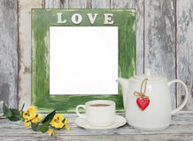 Cup of tea and teapot with heart shape on wooden table. Stock Photography