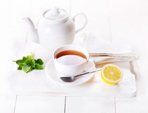 Cup of tea and teapot with lemon and mint Royalty Free Stock Photography