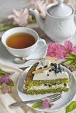 A cup of tea, a teapot and a piece of spinach cake on a table in light colors in retro style stock photos
