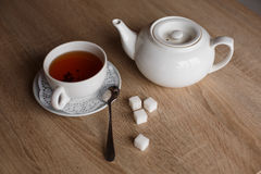 Cup of tea, teapot, spoon and sugar Stock Photo