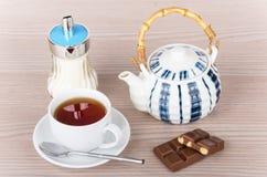 Cup of tea, teapot, sugar bowl and chocolate pieces Stock Photos