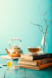 Cup of tea with teapot and vintage books Blue background Stock Images
