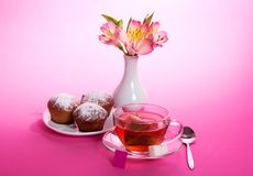 Cup of tea, teaspoon and cupcakes. Cup of tea and sugar on a saucer, a teaspoon, an alstroemeria in a vase, on a pink background Royalty Free Stock Photo