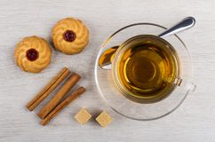 Cup of tea, teaspoon, curabe, cinnamon sticks and sugar Royalty Free Stock Photo