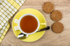 Cup of tea, teaspoon, lumpy sugar on saucer, biscuits Royalty Free Stock Photos