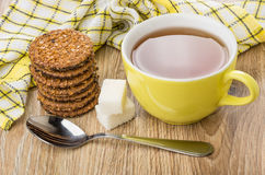 Cup of tea, teaspoon, lumpy sugar, stack of biscuits Stock Image