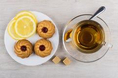 Cup of tea, teaspoon, saucer with curabe and lemon Stock Photos