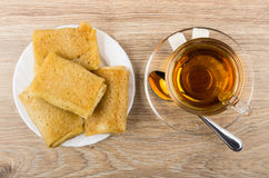 Cup of tea, teaspoon and sugar, pancakes with stuffed Royalty Free Stock Image