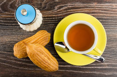 Cup with tea, teaspoon, sugar and two eclairs on table Royalty Free Stock Images
