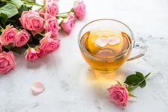 Cup of tea and tender pink roses on a white background.  Royalty Free Stock Photography