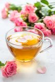 Cup of tea and tender pink roses on a white background.  Royalty Free Stock Images