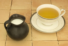 Cup of tea on terracotta table. A cup of tea and milk Jug Stock Photography