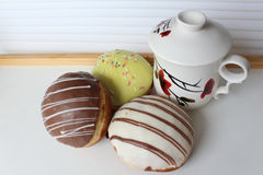 Cup of tea and three multicolored donuts. With different filling on a small table.white background stock photography