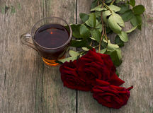 Cup of tea and three red beautiful roses Royalty Free Stock Photo