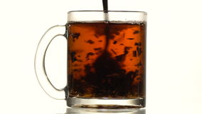 The cup of tea thrown refined sugar. A glass cup of black tea throw refined sugar. Slow motion. Close-up stock footage
