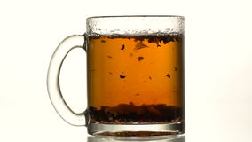 The cup of tea thrown refined sugar. A glass cup of black tea throw refined sugar. Slow motion. Close-up stock video