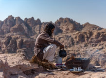 A Cup of Tea. On top of mountains in Petra in Jordan. A Local Bedouin man serving hot cup of tea to guests on top of the mountain Stock Photography