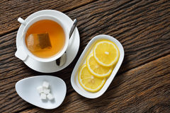 Cup of tea. Top view of cup of tea with tea bag, sugar cube and lemon on wooden table stock image