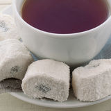 Cup with tea and Turkish delight. White ceramic cup with tea and white Turkish delight Royalty Free Stock Images