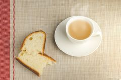 Cup of tea with two bread for breakfast on tablecloth Royalty Free Stock Photos