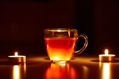 Cup of tea with two small lighting candles Royalty Free Stock Images