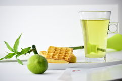 Cup of tea and waffles. On a plate next to a lime and bamboo Royalty Free Stock Images