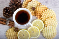 Cup of tea with waffles and cinnamon, lemon, badian, pinecone Royalty Free Stock Photography