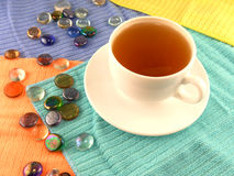 Cup of tea in a white cup with stones on a material background Royalty Free Stock Image