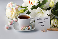 Cup of tea, white lily and colored marshmallow Stock Images