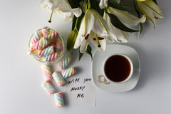 Cup of tea, white lily, colored marshmallow and note Royalty Free Stock Images