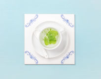 Cup of tea on white tile board over sky-blue background stock photography