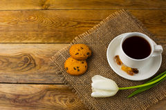 Cup of tea and white tulip on sackcloth, top view Royalty Free Stock Images