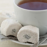 Cup with tea and white Turkish delight. White ceramic cup with tea and white Turkish delight on a napkin Royalty Free Stock Image