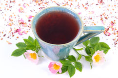 Cup of tea with wild rose flower on white background Royalty Free Stock Photos