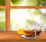 Cup of tea on window on green background close-up Stock Images
