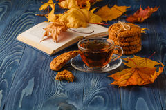Cup of tea wit old book and autumn leaves on wooden table Stock Images