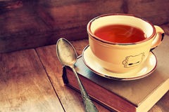 Cup of tea wit old book h autumn leaves and a warm scarf on wooden table Stock Images