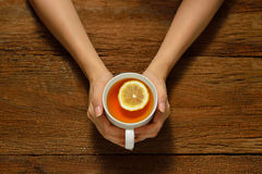 Cup of tea. Woman holding cup of tea with lemon on wooden table Stock Photo