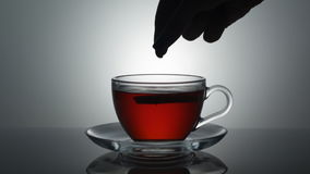 A cup of tea. A woman`s hand puts a piece of lemon in a cup of tea stock video footage