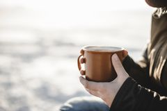 Cup of tea in women`s hands. Beautiful sunny day outdoors. End of the winter and warm tea stock images