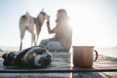 Cup of tea on the wood texture. Girl with her dog on the background royalty free stock photos