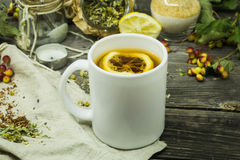 Cup of tea on wooden background with lemon and herbs. Beautiful Cup of tea on wooden background with lemon and herbs Stock Photos