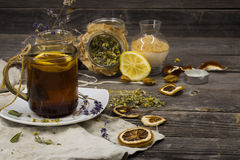 Cup of tea on wooden background with lemon and herbs. Beautiful Cup of tea on wooden background with lemon and herbs Stock Photography