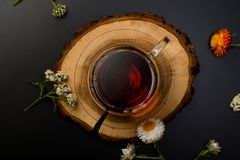 Cup of tea on a wooden desks. A glass cup of tea on the wooden desks with flowers and some dried leaves stock photography