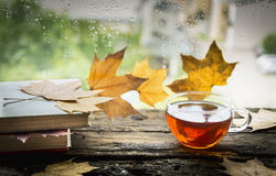 Cup of tea on a wooden rain window sill with books and autumn leaves on a natural background