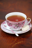 A cup of tea on a wooden table. Pink cup of tea with floral pattern served on a wooden table Royalty Free Stock Photo
