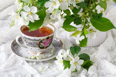 Cup of tea on wooden table and apple blossom. Tea time concept. Breakfast tea cup served with flowers. Stock Images
