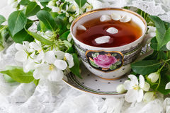 Cup of tea on wooden table and apple blossom. Tea time concept. Breakfast tea cup served with flowers. Royalty Free Stock Images